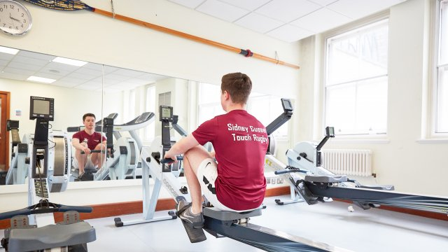 A student using a rowing machine in the Sidney gym